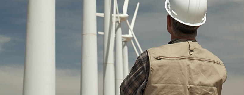 Man looking up at turbines on wind farm